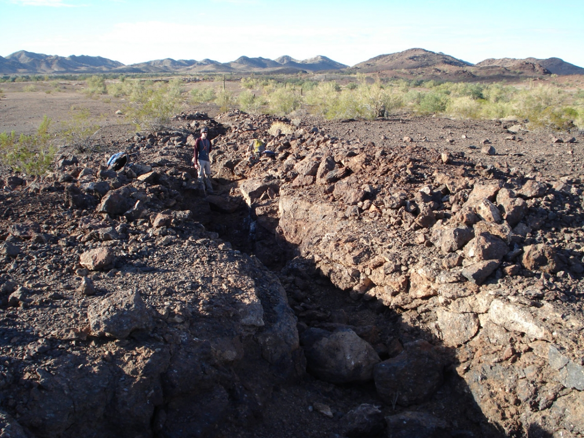Photograph of partially mined, manganese oxide – barite vein in the northern Plomosa Mountains near Bouse, Arizona. AZGS volunteer Trevor Cole is shown for scale. Photography by Jon Spencer.